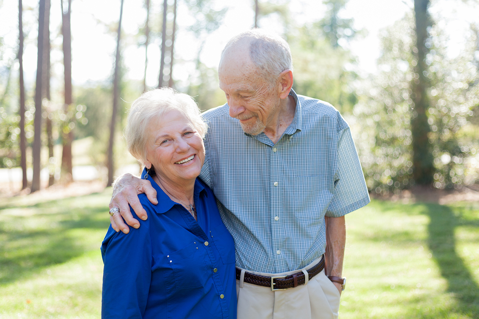 An elderly man has his arm around an elderly woman.