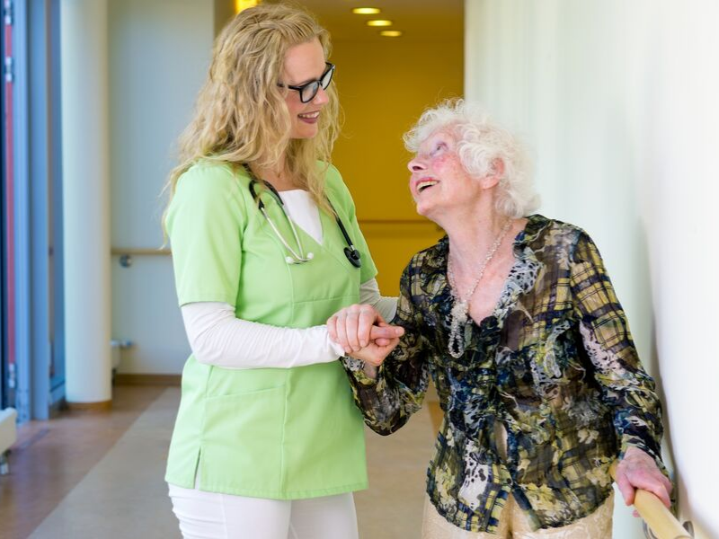 nurse in green scrubs helping older woman walk the hallway