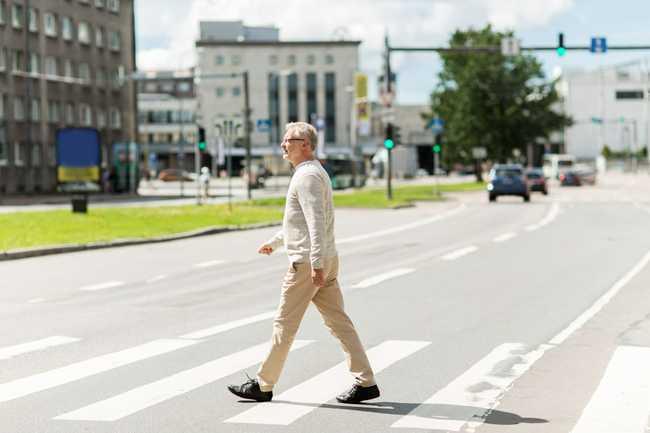 Elderly man walking across the street