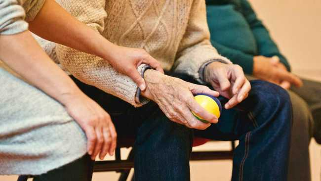 respite care provider holding elderly man's arm with tennis ball